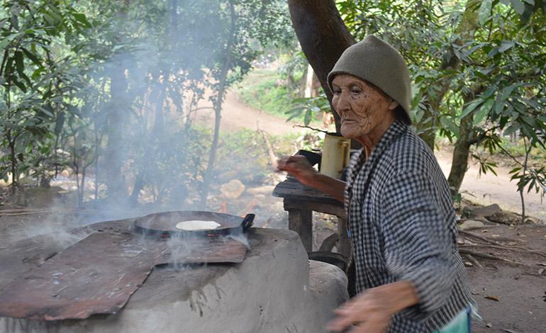 Doña María junto al fogón humeante. La tortilla lista en el comal.