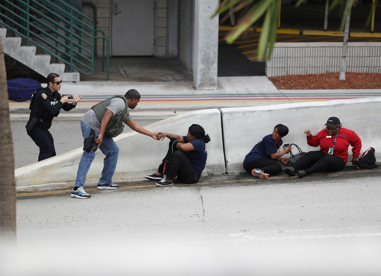 FORT LAUDERDALE, FL - JANUARY 06: Police assist people seeking cover outside of Terminal 2 at Fort Lauderdale-Hollywood International airport after a shooting took place near the baggage claim on January 6, 2017 in Fort Lauderdale, Florida. Officials are reporting that five people wear killed and eight wounded in an attack by a single gunman. (Photo by Joe Raedle/Getty Images)