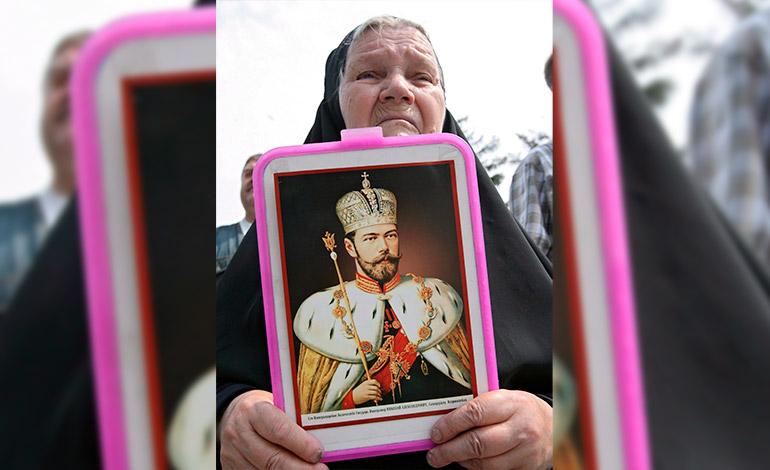 Una mujer sostiene el retrato del último zar de Rusia, Nicolás II, durante una misa por el noventa aniversario de la ejecución de la familia real en Moscú. El zar y su familia, que fueron asesinados por los bolcheviques, fueron canonizados iglesia ortodoxa rusa. EFE/Sergei Ilnitsky