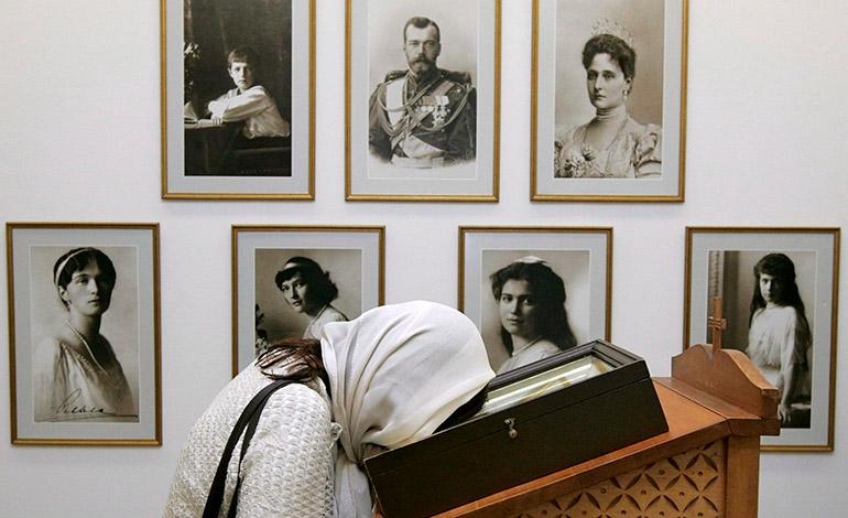 Una mujer coloca su cabeza cerca de una fotografía del zar Nicolás II y su familia durante una exposición en la catedral de Cristo Salvador con motivo del 90 aniversario de su ejecución en Moscú, Rusia. EFE/Sergei Chirikov