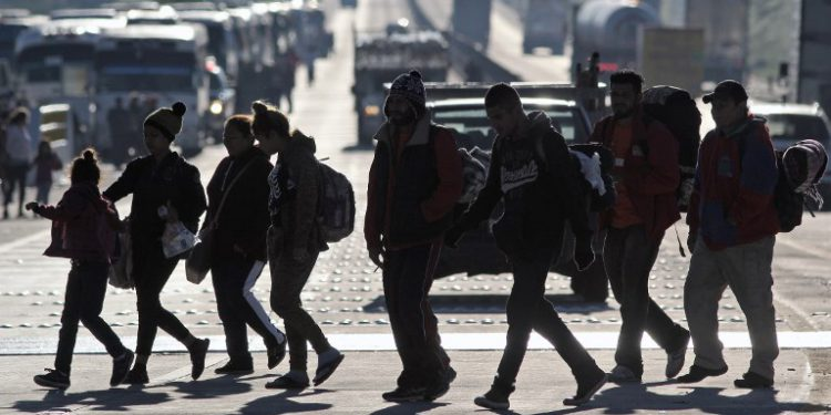 """Migrants from poor Central American countries -mostly Hondurans- moving towards the United States in hopes of a better life, at seen at a tollbooth on the road between Zapopan and Tequila in the Mexican state of Jalisco, on their trek north, on November 13, 2018. - Defense Secretary Jim Mattis said Tuesday he will visit the US-Mexico border, where thousands of active-duty soldiers have been deployed to help border police prepare for the arrival of a """"caravan"""" of migrants. (Photo by ULISES RUIZ / AFP)"""