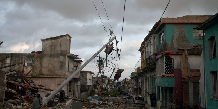 Resident stand amid the debris of buildings left after the passage of a tornado in Havana, on January 28, 2019. - A rare and powerful tornado that struck Havana killed three people and left 172 injured, Cuban President Miguel Diaz-Canel said early Monday. (Photo by YAMIL LAGE / AFP)