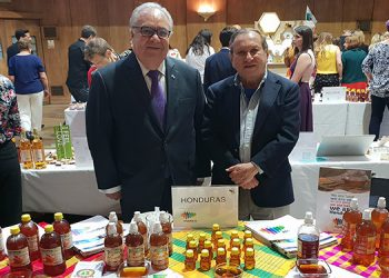 """El embajador de Honduras, Iván Romero Martínez; y el embajador Asesor de SRECI, junto al stand donde fue exhibida la miel """"catracha""""."""