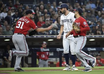 SAN DIEGO, CA - JUNE 8: Eric Hosmer #30 of the San Diego Padres is tagged out by Max Scherzer #31 of the Washington Nationals as Anthony Rendon #6 looks on during the second inning of a baseball game at Petco Park June 8, 2019 in San Diego, California. Hosmer was caught off third base.   Denis Poroy/Getty Images/AFP