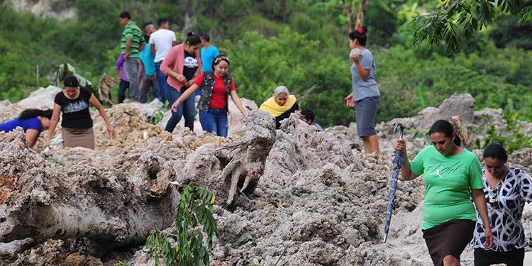 Los pobladores caminan por los escombros a falta de carretera en la zona de deslave.