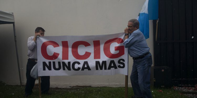 "Men place a sign that reads in Spanish ""CICIG never again,"" outside of the United Nations International Commission Against Impunity, CICIG, to celebrate the end of its 12-year mission, in Guatemala City, Tuesday, Sept. 3, 2019. CICIG is closing its operation after 12 years. It brought to trial three former presidents and hundreds of businessmen, officials, judges and individuals accused of corruption. (AP Photo/Moises Castillo)"