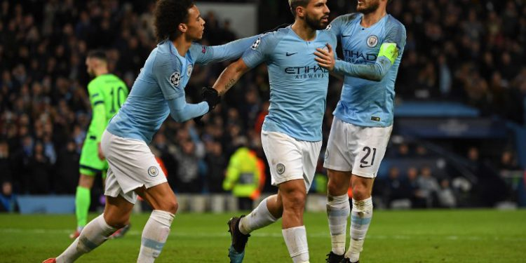 Manchester City's Argentinian striker Sergio Aguero (C) celebrates with Manchester City's German midfielder Leroy Sane (L) and Manchester City's Spanish midfielder David Silva (R) after scoring the opening goal from the penalty spot during the UEFA Champions League round of 16 second leg football match between Manchester City and Schalke 04 at the Etihad Stadium in Manchester, north west England, on March 12, 2019. (Photo by Paul ELLIS / AFP)
