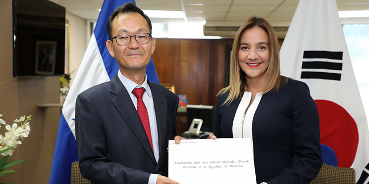 El nuevo embajador de Corea, Jaehyun Shim, entrega las copias de estilo a Nelly Jerez.