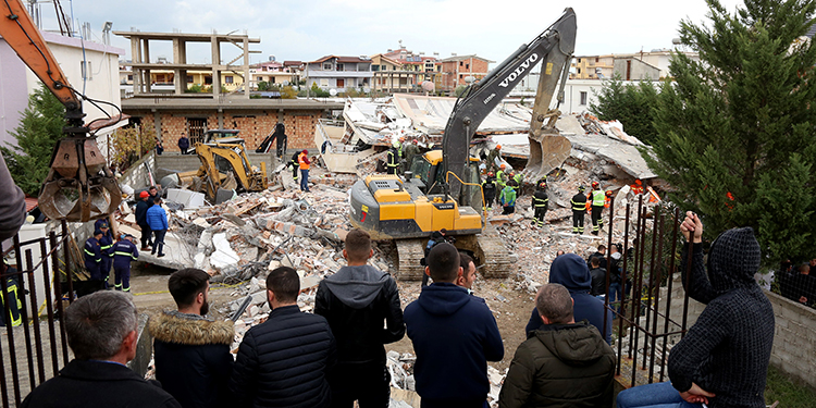 People watch as Italian rescuers look for bodies through the rubble of a collapsed building on November 27, 2019 in Thumane, northwest of the capital Tirana, after an earthquake hit Albania. - Albania was in national mourning on November 27 as emergency workers continued to pull bodies from the ruins of buildings gutted by a violent earthquake, with nearly 30 dead found so far and more than 40 rescued alive. Tirana declared a state of emergency in the areas hardest-hit by the November 26 pre-dawn earthquake: the coastal city of Durres and the town of Thumane, where victims were trapped by toppled buildings. (Photo by Gent SHKULLAKU / AFP)