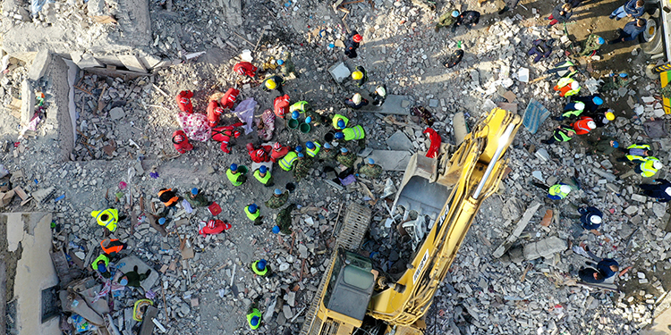 This aerial photo taken on November 27, 2019, shows rescue workers as they remove the bodies of a dead couple from the ruins of a collapsed building in Thumane, northwest of the capital Tirana, after an earthquake hit Albania. - Albania was in national mourning on November 27 as emergency workers continued to pull bodies from the ruins of buildings gutted by a violent earthquake, with nearly 30 dead found so far and more than 40 rescued alive. Tirana declared a state of emergency in the areas hardest-hit by the November 26 pre-dawn earthquake: the coastal city of Durres and the town of Thumane, where victims were trapped by toppled buildings. (Photo by Gent SHKULLAKU / AFP)