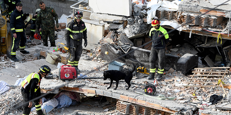 Italian rescuers search for survivors through the rubble of a collapsed building on November 27, 2019 in Thumane, northwest of the capital Tirana, after an earthquake hit Albania. - Albania was in national mourning on November 27 as emergency workers continued to pull bodies from the ruins of buildings gutted by a violent earthquake, with nearly 30 dead found so far and more than 40 rescued alive. Tirana declared a state of emergency in the areas hardest-hit by the November 26 pre-dawn earthquake: the coastal city of Durres and the town of Thumane, where victims were trapped by toppled buildings. (Photo by Gent SHKULLAKU / AFP)