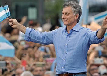 Argentine President Mauricio Macri waves as he holds Argentinian flags during a farewell rally at the Casa Rosada presidential palace at Plaza de Mayo square, in Buenos Aires, on December 7, 2019. - Opposition President-elect Alberto Fernandez takes office on December 10. (Photo by ALEJANDRO PAGNI / AFP)