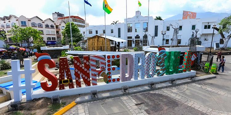 """Colocadas frente al Palacio Municipal y con el imponente Merendón de fondo, las letras """"#SanPedroSula"""" dan la bienvenida a las fiestas navideñas."""