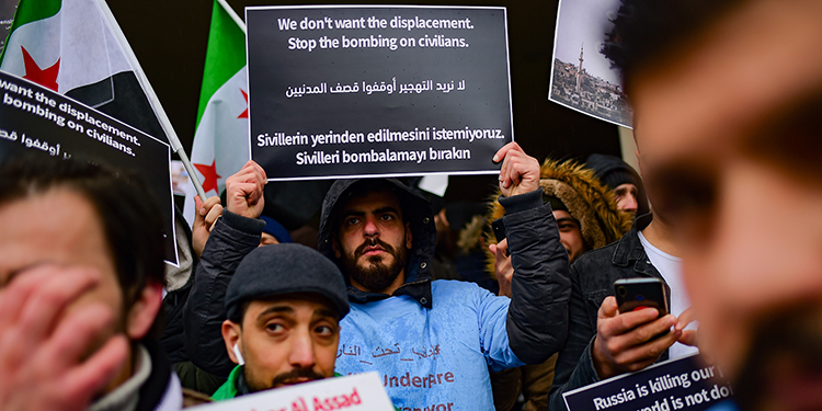 "Protesters chant slogans and hold placards reading ""We don't want the displacement, stop the bombing on civilians"" during a protest against Syrian military operation in the rebel bastion of Idlib, northwestern Syria, taking place near the Russian Consulate, in Istanbul, on December 28, 2019. - Around 300 protesters -- mostly Syrians living in Turkey -- gathered in a neighbourhood some 300 metres from the Russian consulate in Istanbul, AFP journalists on the ground said. Alarmed by a new wave of refugees near its border, Turkey this week sent a delegation to Moscow in a bid to press for a fresh ceasefire deal. (Photo by Yasin AKGUL / AFP)"