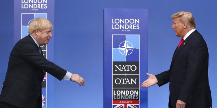 British Prime Minister Boris Johnson, left, reaches out to shake hands with U.S. President Donald Trump at the official arrivals for a NATO leaders meeting at The Grove hotel and resort in Watford, Hertfordshire, England, Wednesday, Dec. 4, 2019. NATO Secretary-General Jens Stoltenberg rejected Wednesday French criticism that the military alliance is suffering from brain death, and insisted that the organization is adapting to modern challenges. (AP Photo/Francisco Seco)