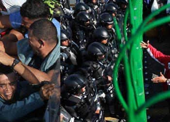 """Miles de migrantes centroamericanos, en su mayoría hondureños, intentaron entrar a México a empujones, pero las autoridades mexicanas cerraron la verja para poner """"orden"""" en el flujo de entrada."""