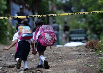 Two girls walking to school are crossing the yellow police line at crime scene in front of their school. A man of 24 as he left his house on his way to work in the municipality of San Marcos, San Salvador. Gangs in El Salvador have increased their presence in schools across the country, who have accomplished much even recruiting young people based on threats