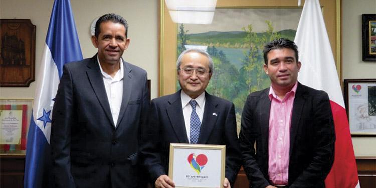 El embajador Norio Fukuta sostiene el logo del 85 aniversario de diplomacia entre Honduras y Japón.
