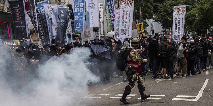 Tear gas is fired by police during a pro-democracy march in Hong Kong on January 1, 2020. - Tens of thousands of protesters marched in Hong Kong during a massive pro-democracy rally on New Year's Day, looking to carry the momentum of their movement into 2020. (Photo by ISAAC LAWRENCE / AFP)