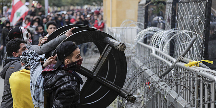 Anti-government protesters attempt to break through the security barrier in the central downtown district of the Lebanese capital Beirut near the parliament headquarters during clashes with security forces on January 18, 2020. (Photo by ANWAR AMRO / AFP)