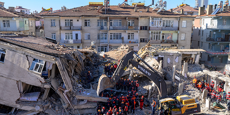 Rescue workers remove corpses from the rubble of a building after an earthquake in Elazig, eastern Turkey, on January 26, 2020. - Rescue workers raced against time on January 25 to find survivors under the rubble after a powerful earthquake claimed 22 lives and left more than 1,200 injured in eastern Turkey. The magnitude 6.8 quake struck in the evening of January 24, with its epicentre in the small lakeside town of Sivrice in Elazig province, and was felt across neighbouring countries. (Photo by BULENT KILIC / AFP)