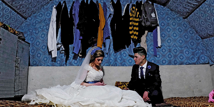 Sundus Garis (L), 16, and Farid Mallo, 19, both from the beleaguered Yazidi community who were displaced from northern Iraq's Sinjar region, are pictured during their wedding ceremony inside a tent in the Kabarto 2 camp for internally displaced people near the northernwestern Iraqi Kurdish city of Dohuk, not far from the border with Turkey, on January 23, 2020. - Sinjar, a region west of the northern Iraqi city of Mosul that was overrun by the extremist Islamic State (IS) group five years ago, is the historic home of the Yazidi minority which under went a brutal campaign waged by IS jihadists who forced children to become soldiers and used thousands of women as sex slaves. Only a sliver of Sinjar's native population of 500,000 Yazidis has returned since their region was taken back by Iraqi forces from IS in 2017, with the rest saying persistent destruction, the lack of services and the tense security situation have kept them in camps. (Photo by SAFIN HAMED / AFP)