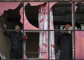 Afganos retiran los vidrios rotos de una ventaja en una casa afectada por la explosión de una bomba en Kabul, Afganistán.