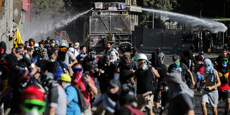 A police water cannon sprays on demonstrators during a protest against the government of President Sebastian Pinera, in Santiago, on February 7, 2020. (Photo by JAVIER TORRES / AFP)