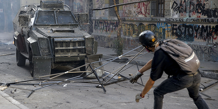 A demonstrator throws objects at a riot police vechicle during a protest against the government of President Sebastian Pinera, in Santiago, on February 7, 2020. (Photo by JAVIER TORRES / AFP)