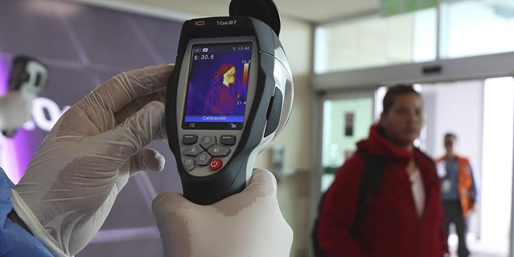 Personal del Ministerio de Salud monitorea la temperatura corporal de los viajeros en el aeropuerto Mariscal Sucre en Quito, Ecuador.