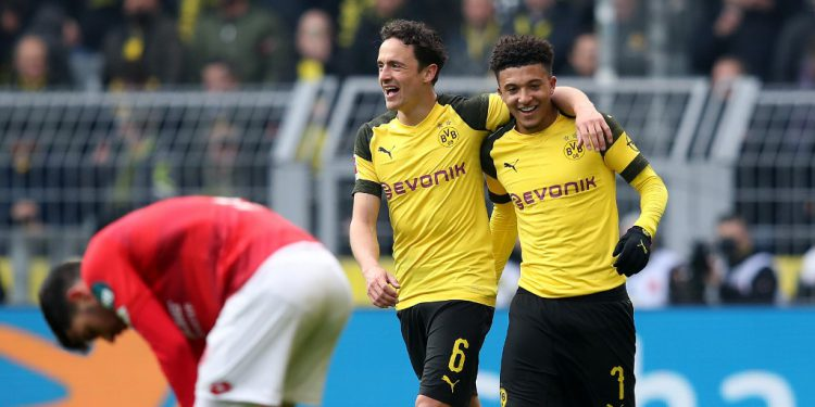Dortmund's English midfielder Jadon Sancho (R) celebrates after scoring his team's second goal with Dortmund's Danish midfielder Thomas Delaney (L) during the German First division Bundesliga football match between Borussia Dortmund and Mainz 05 in Dortmund on April 13, 2019. (Photo by Ronny Hartmann / AFP) / DFL REGULATIONS PROHIBIT ANY USE OF PHOTOGRAPHS AS IMAGE SEQUENCES AND/OR QUASI-VIDEO