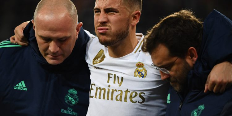 Real Madrid's Belgian forward Eden Hazard gestures in pain during the UEFA Champions League group A football match Real Madrid against Paris Saint-Germain FC at the Santiago Bernabeu stadium in Madrid on November 26, 2019. (Photo by GABRIEL BOUYS / AFP)