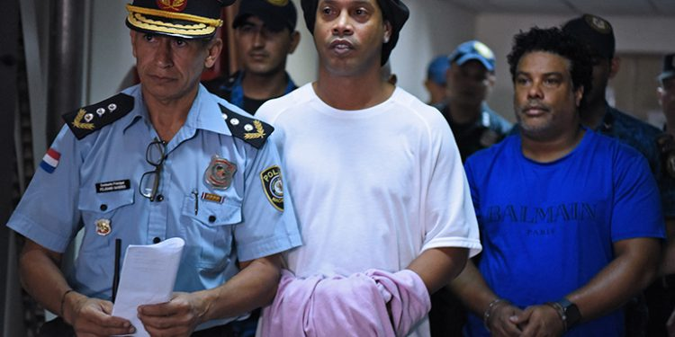 Brazilian retired football player Ronaldinho (C) and his brother Roberto Assis (R) arrive at Asuncion's Justice Palace to appear before a public prosecutor who will decide whether to grant them bail or not following their irregular entry to the country, in Asuncion, on March 7, 2020. - Former Brazilian football star Ronaldinho and his brother have been detained in Paraguay after allegedly using fake passports to enter the South American country, authorities said Wednesday. (Photo by Norberto DUARTE / AFP)