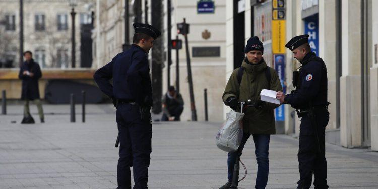 La policía controla a un hombre en la avenida Champs-Elysées de París, martes 17 de marzo de 2020. (AP foto/Christophe Ena)