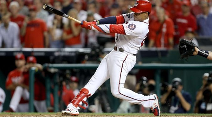 WASHINGTON, DC - OCTOBER 01: Juan Soto #22 of the Washington Nationals hits a single to right field to score 3 runs off of an error by Trent Grisham #2 of the Milwaukee Brewers during the eighth inning in the National League Wild Card game at Nationals Park on October 01, 2019 in Washington, DC.   Rob Carr/Getty Images/AFP == FOR NEWSPAPERS, INTERNET, TELCOS & TELEVISION USE ONLY ==