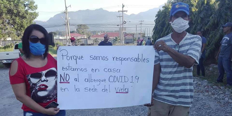 Colonos portando pancartas en contra que las personas señaladas para que no fuesen albergadas en la sede del club deportivo Vida.