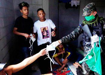Militares hondureños reparten mascarillas a los prisioneros de la cárcel de Tamara./ Jorge Carreras (AFP)