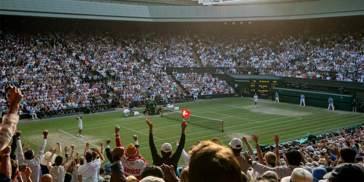 Spectators on Centre Court celebrate as Roger Federer (SUI) wins the semi-final of the Gentlemen's Singles over Rafael Nadal (ESP). The Championships 2019. Held at The All England Lawn Tennis Club, Wimbledon. Day 11 Friday 12/07/2019. Credit: AELTC/Thomas Lovelock.