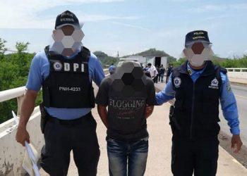 El menor de edad junto a detectives de la DPI, cuando cruzaban el puente de Guasaule que une a Honduras y Nicaragua.
