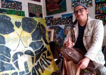 En su taller en Valle de Ángeles, el pintor Denis Berríos posa junto a una de sus últimas pinturas, inspirada en las medidas de bioseguridad por el COVID-19.