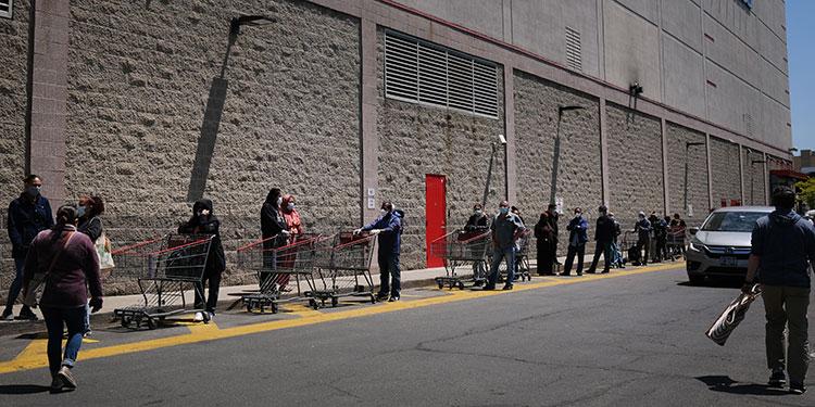 La gente espera en la fila fuera de un Costco en Brooklyn.Con un número limitado de tiendas abiertas en Nueva York y los nuevos requisitos de distanciamiento social, muchos supermercados siguen viendo largas colas.