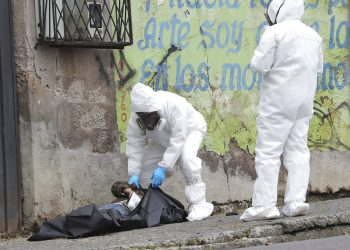 A forensic investigator places into a cadaver bag the body of a man who died after collapsing in the street in Quito, Ecuador, Tuesday, May 5, 2020. According to Police Captain Diego Lopez the man died from the new coronavirus. (AP Photo/Dolores Ochoa)