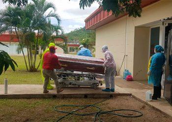 Parientes reciben bajo protocolo de bioseguridad el cuerpo de una de las víctimas de COVID-19.