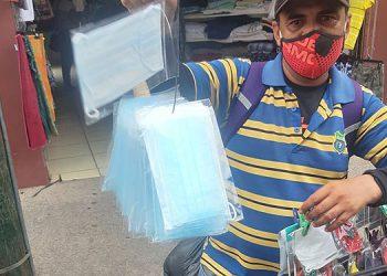 Hombre y mujeres se dedican a vender mascarillas quirúrgicas hasta por cinco lempiras cada una en toda la ciudad.