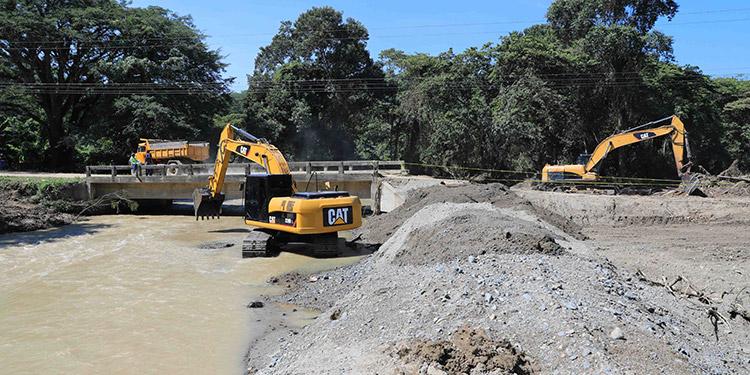 """Trabajos de dragado y otras labores de rehabilitación en el río """"El Águila"""" para garantizar que el paso por el puente del mismo nombre no se vuelva a interrumpir debido a las crecidas."""