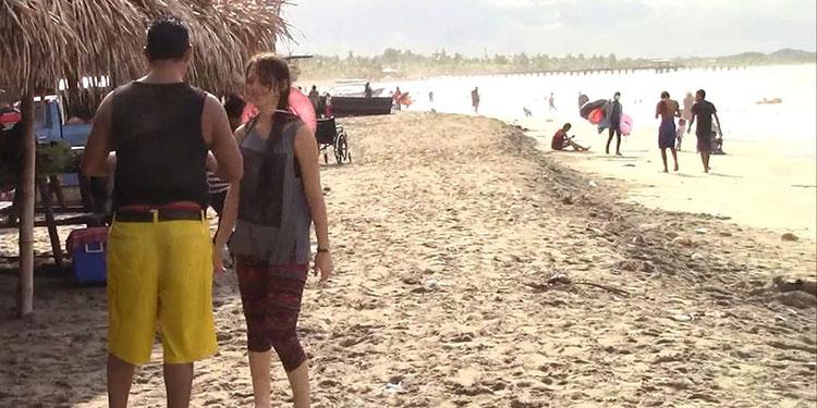 Ni la lluvia detiene a bañistas en playas de Tela