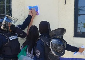 Agentes policiales impidieron que jóvenes protestantes pegaran afiches en la sede policial.