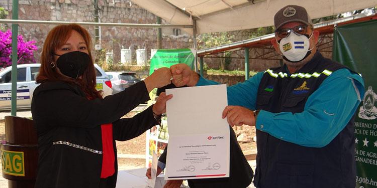El ministro de la SAG, Mauricio Guevara, entrega a la directora de Comunicaciones, Yamileth Romero, su respectivo diploma.