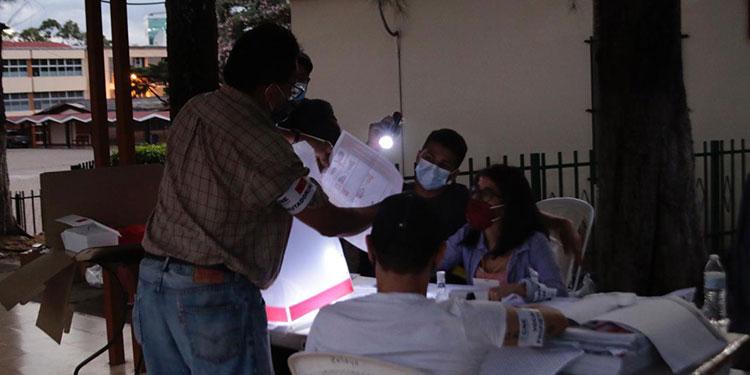 Un apagón repentino obligó a los encargados de mesa de un centro de votación a iluminarse con el celular.