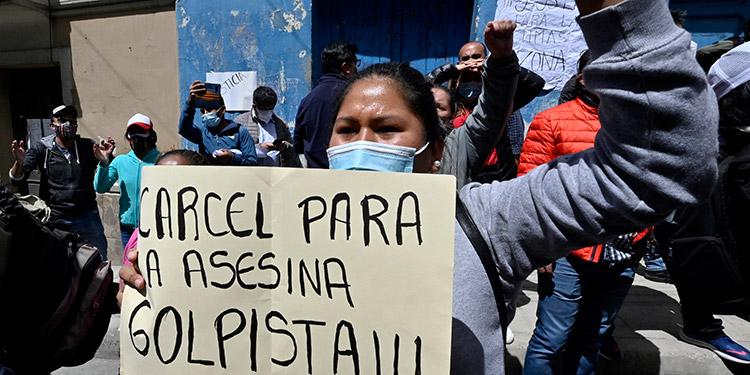 Un grupo de personas hace una vigilia en las puertas de la Fuerza Especial de Lucha Contra el Crimen en La Paz a la espera de conocer la determinación de la audiencia de las exautoridades aprehendidas, mientras otras apoyan a la expresidenta Jeanine Áñez y se alistan cabildos para el lunes. (LASSERFOTO  AFP)